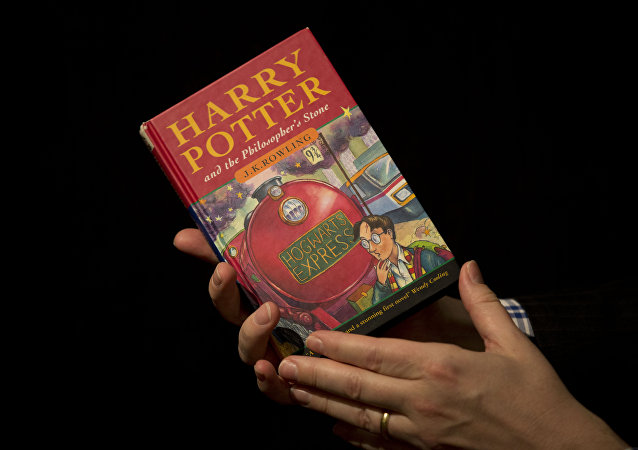 Sotheby's director of the department of printed books and manuscripts Dr Philip Errington poses for photographers with a first edition copy of the first Harry Potter book Harry Potter and the Philosopher's Stone containing annotations and illustrations by author J.K. Rowling, during a photocall organized for the media at the auction house's premises in London. (File)