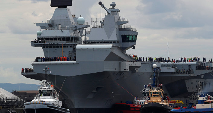 The British aircraft carrier HMS Queen Elizabeth is pulled from its berth by tugs before its maiden voyage, in Rosyth, Scotland, Britain June 26, 2017.