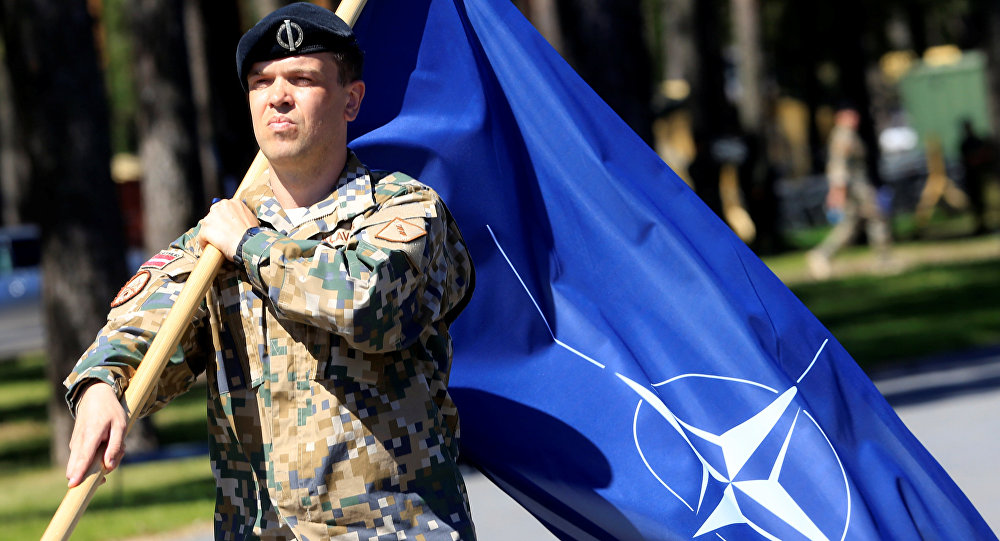 A Latvian Army soldier walks with the NATO flag during the official welcoming ceremony of the NATO Canadian-led Enhanced Forward Presence (EFP) combat battalion in Adazi, Latvia June 19, 2017