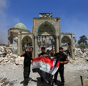 Members of the Counter Terrorism Service pose for a picture with an Iraqi flag in front of the ruins of Grand al-Nuri Mosque at the Old City in Mosul, Iraq, June 30, 2017