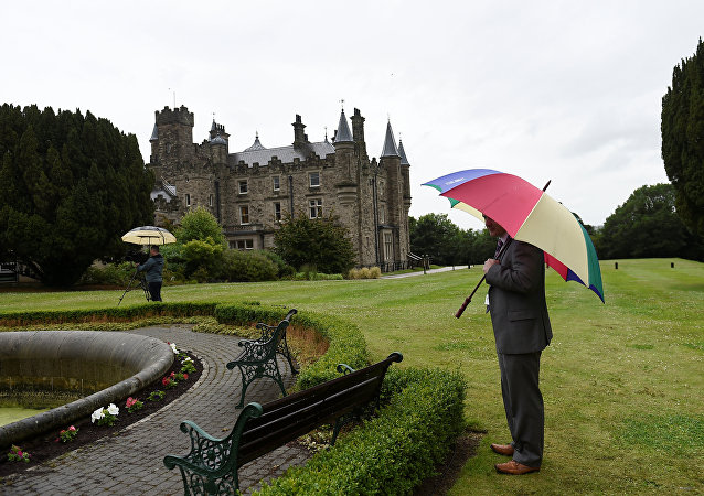 A journalist waits in the rain outside Stormont Castle in Belfast, Northern Ireland June 29, 2017.