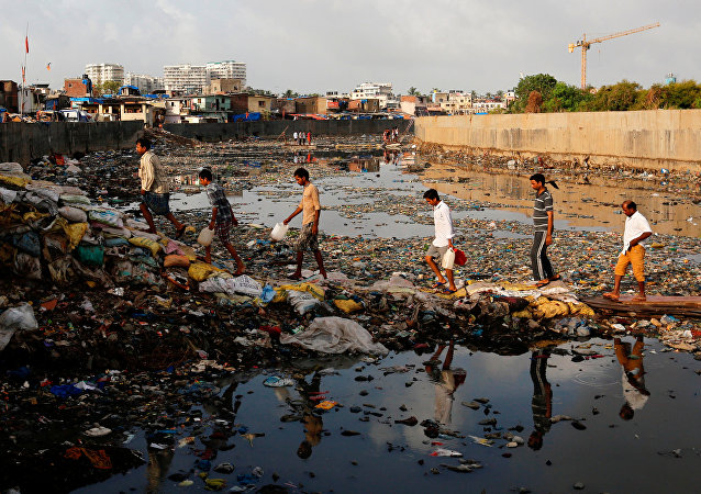 Residents cross a polluted water canal at a slum on the World Environment Day in Mumbai, India, June 5, 2017