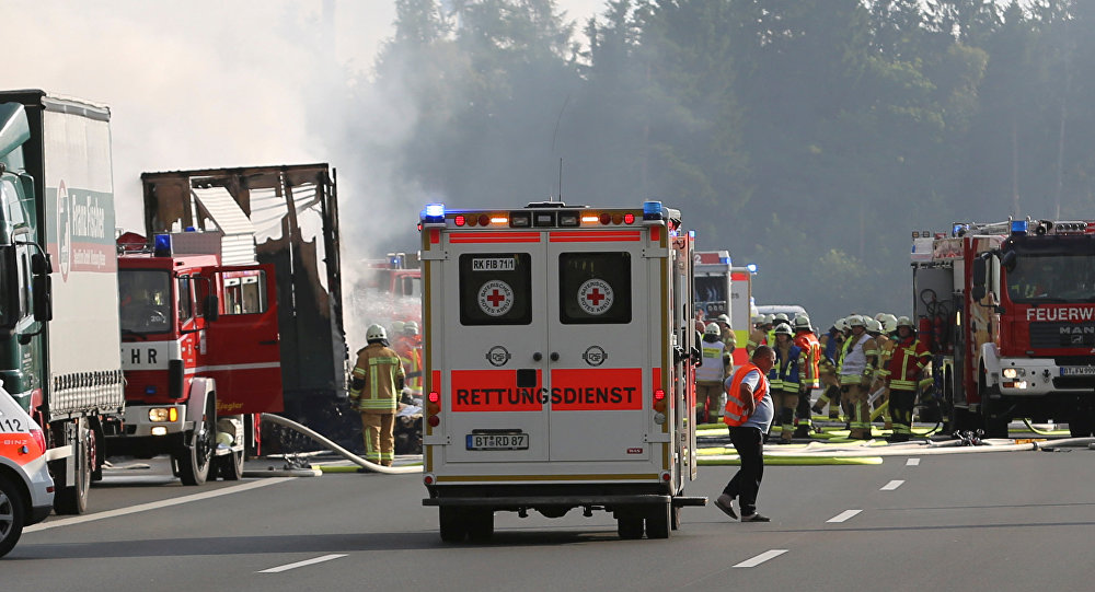 Ambulance cars and fire engines near a bus where a coach burst into flames after colliding with a lorry on a motorway near Muenchberg, Germany, July 3, 2017.