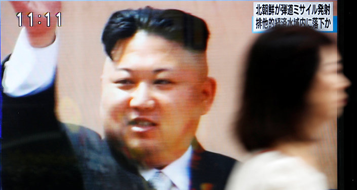 A woman walks past a street monitor in Tokyo, Japan, reporting that North Korea had fired a ballistic missile, in this photo taken by Kyodo July 4, 2017.