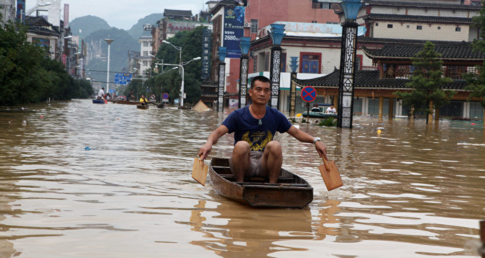A man makes his way with a wooden boat through a flooded area in Liuzhou, Guangxi province, China July 2, 2017.