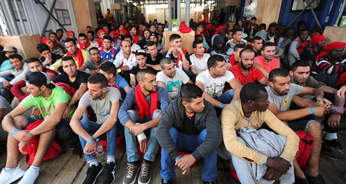 Migrants wait to disembark from the Vos Hestia ship as they arrive at the Crotone harbour, after being rescued by a Save the Children crew in the Mediterranean sea off the Libya coast, in Crotone, Italy June 21, 2017.