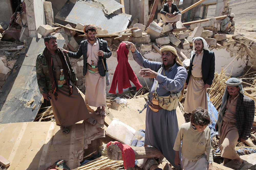 A man center, holds house destroyed by a Saudi-led airstrikes in outskirts of Sanaa, Yemen, Thursday, Feb. 16, 2017.