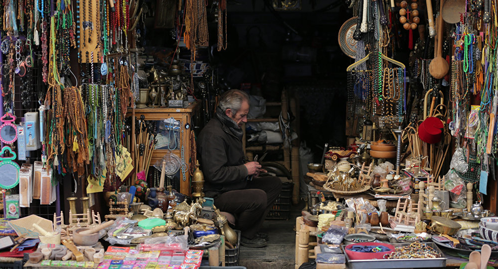 A Syrian man sits inside his handicraft shop in the Syrian capital, Damascus