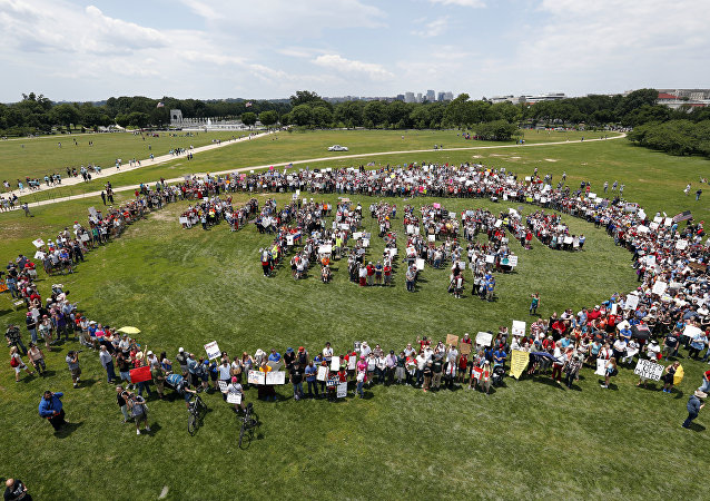 Protesters encircle a group standing to form letters that spell Impeach Trump, during a rally to protest President Donald Trump and his policies, on the National Mall, Saturday, June 3, 2017, in Washington