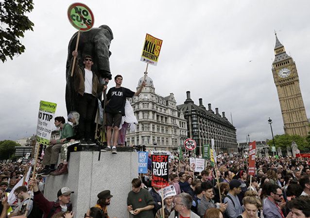 Demonstrators hold placards in Parliament Square as they march during a protest against the Conservative Government and it's austerity policies in London, Saturday, June 20, 2015.