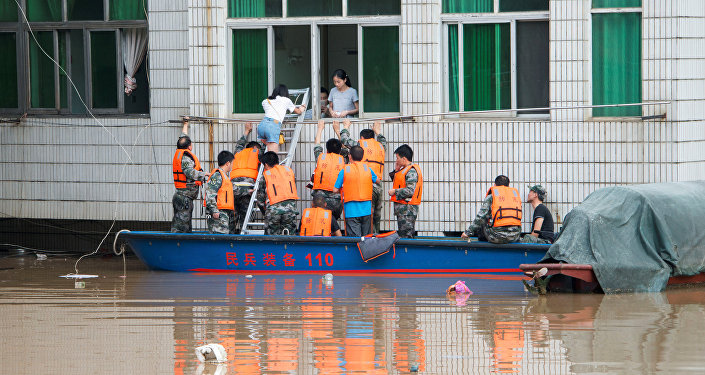 Rescuers evacuate people during a flood in Xinshao county, Hunan province, China, July 2, 2017