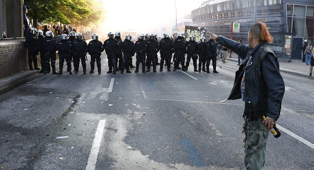 A protester stands in front of German riot police during the demonstrations during the G20 summit in Hamburg, Germany, July 6, 2017