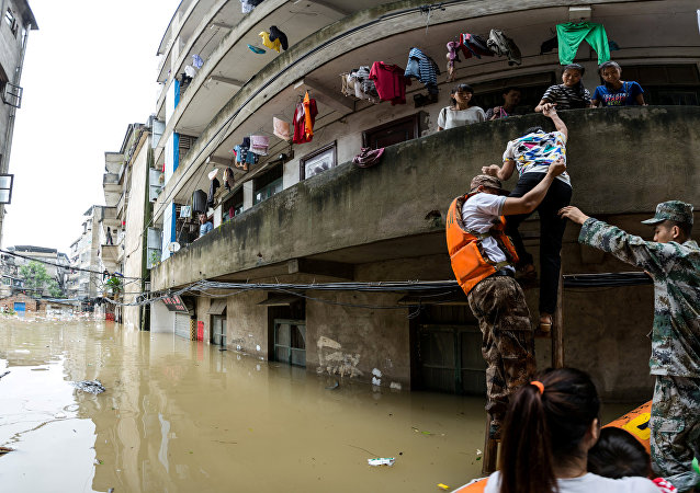 Rescuers transfer residents with a boat at a flooded area in Guilin, Guangxi province, China July 2, 2017. Picture taken July 2, 2017