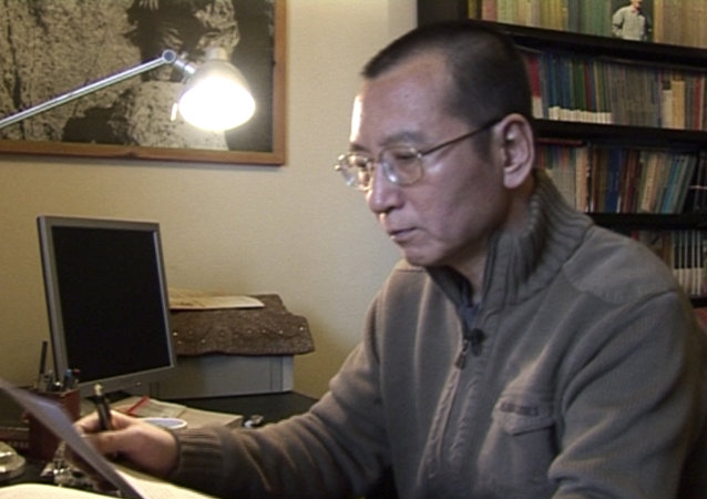 In this image taken from Jan 6, 2008, video footage by AP Video, Liu Xiaobo looks at documents in his home in Beijing, China.