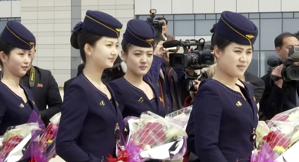 In this image taken from video, Air Koryo cabin crew wait with flowers on tarmac for the airline's first flight from Dandong, at Sunan airport in Pyongyang, North Korea Tuesday, March 28, 2017.