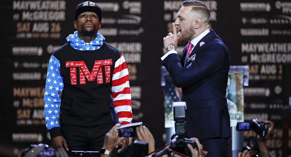 Floyd Mayweather Jr., left, and Conor McGregor pause for photos during a news conference at Staples Center Tuesday, July 11, 2017, in Los Angeles.