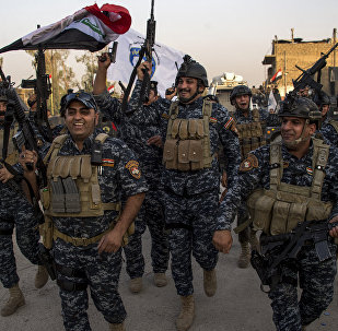 Members of the Iraqi federal police forces celebrate in the Old City of Mosul on July 10, 2017 after the government's announcement of the liberation of the embattled city from Daesh fighters.