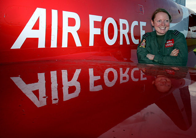 Flight Lieutenant Kirsty Moore poses in front of a Hawk aircraft at the Royal Air Force base at Scampton, England, Thursday Nov. 12, 2009, after being named as the first female pilot to serve with the Red Arrows, the RAF's aerobatic team.