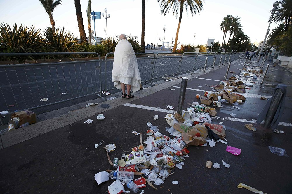 A man walks through debris scatterd on the street the day after a truck ran into a crowd at high speed killing scores celebrating the Bastille Day July 14 national holiday on the Promenade des Anglais in Nice, France, July 15, 2016.