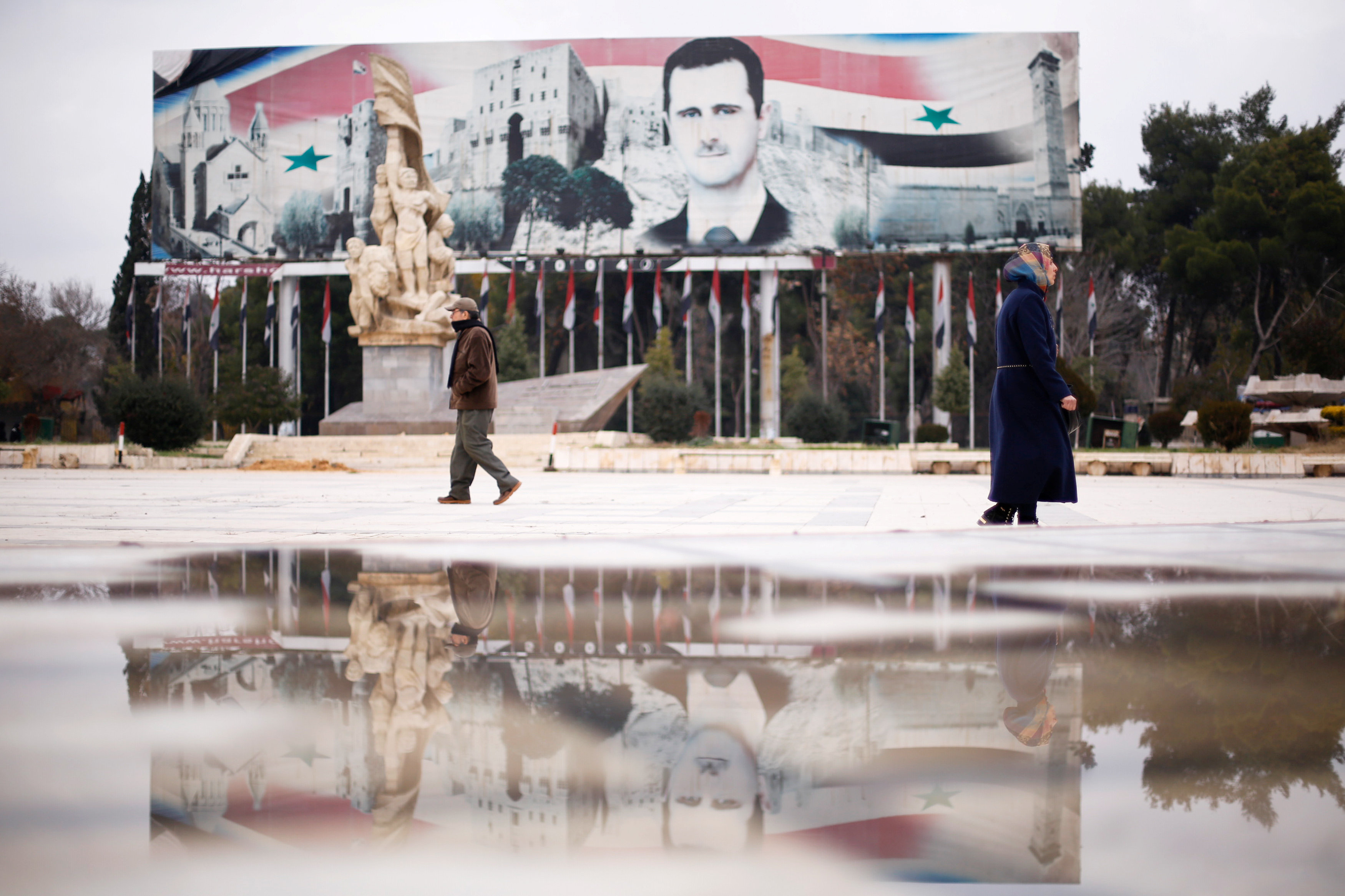 People walk past a billboard depicting Syria's President Bashar al-Assad at Saadallah al-Jabri Square, in the government controlled area of Aleppo, Syria December 17, 2016