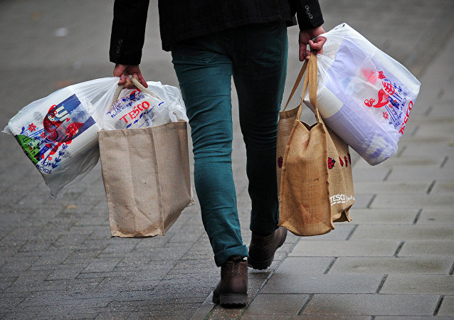 Man carries food shopping bags in Britain.