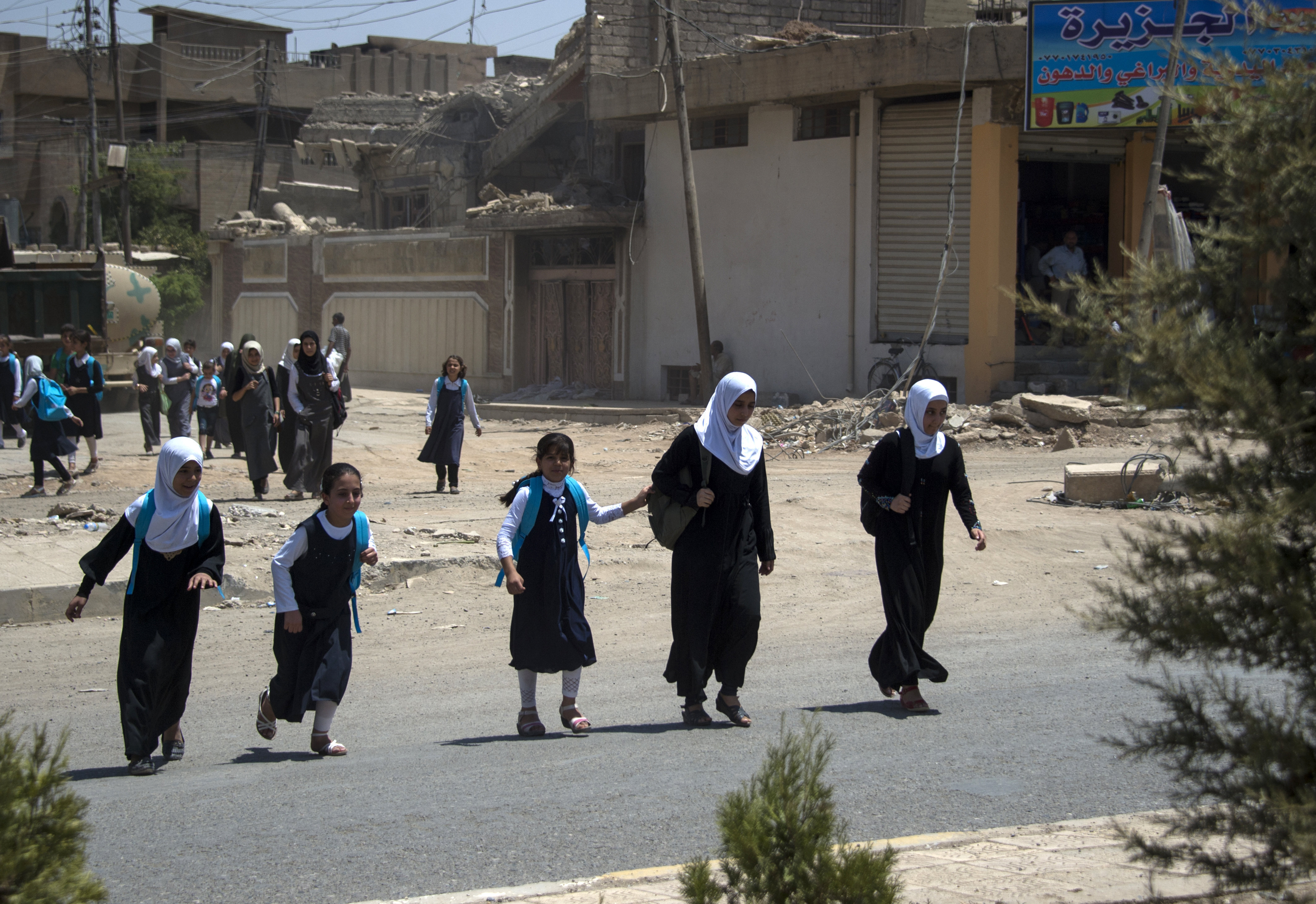 Iraqi girls walk back from school in west Mosul on July 12, 2017 after the government declared it had driven the Islamic State (IS) group jihadists from their one-time top stronghold.
