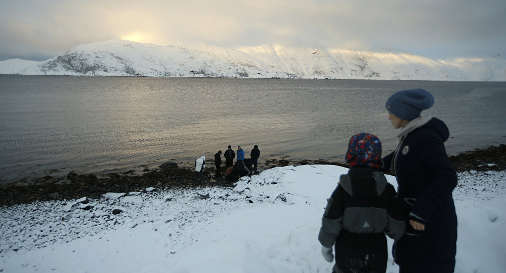 In this photo taken Tuesday, Feb. 2, 2016 asylum seeker Lima Yosufi with her son Roman look out on the view on the island of Seiland, northern Norway, near her temporary accommodation at the Altnes camp.