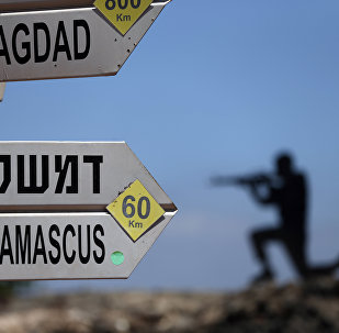 A sculpture of an Israeli soldier standing guard is seen next to a sign for tourists showing the distance to Damascus and Baghdad at an army post on Mount Bental in the Israeli-annexed Golan Heights on June 23, 2015.