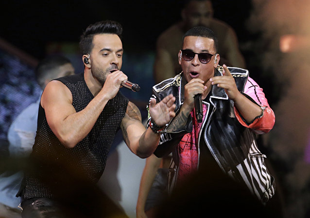 FILE - In this April 27, 2017 file photo, singers Luis Fonsi, left and Daddy Yankee perform during the Latin Billboard Awards in Coral Gables, Fla. Malaysia has banned their hit song Despacito on state radio and television, though it might be hard to slow the song's record-breaking popularity.