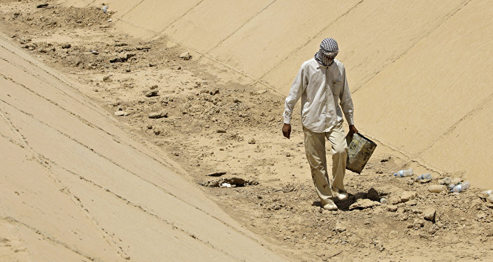 In this photo taken Thursday, July 9, 2009, Abbas Mohammed, walks throw a dray canal in Latifiyah, about 30 kilometers (20 miles) south of Baghdad, Iraq. Below-average rainfall and insufficient water in the Euphrates and Tigris rivers - something the Iraqis have blamed on dams in neighboring Turkey and Syria - have left Iraq bone-dry for a second straight year.
