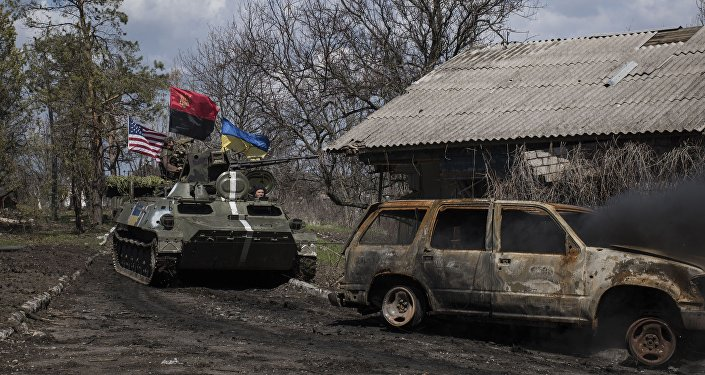 Ukrainian servicemen ride in an armored vehicle, with Ukrainian and U.S. flags and nationalist group Right Sector flag, near a destroyed car in Shyrokyne, eastern Ukraine, Wednesday, April 15, 2015