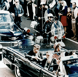 President Kennedy in the limousine in Dallas, Texas, on Main Street, minutes before the assassination. Also in the presidential limousine are Jackie Kennedy, Texas Governor John Connally, and his wife, Nellie