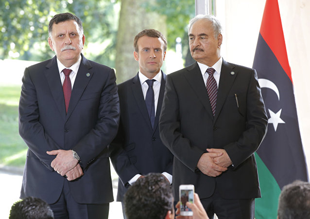 Libya's Prime Minister Fayez al-Sarraj of the U.N.-backed government, left, France's President Emmanuel Macron, center, and General Khalifa Hifter of the Egyptian-backed commander of Libya's self-styled national army shake hands listen to France's President Emmanuel Macron after a declaration at the Chateau of the La Celle-Saint-Cloud, west of Paris, France, Tuesday, July 25, 2017.