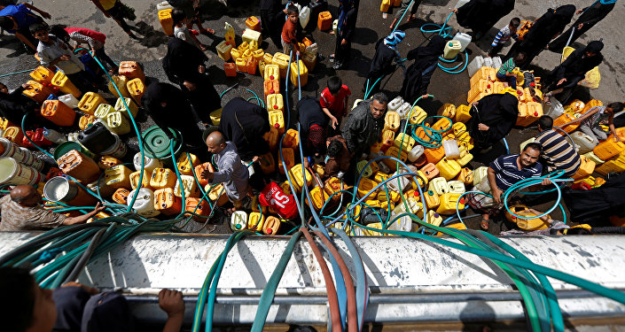 People gather to fill up their jerrycans with drinking water from a charity tanker truck, amid a cholera outbreak, in Sanaa, Yemen, July 12, 2017.