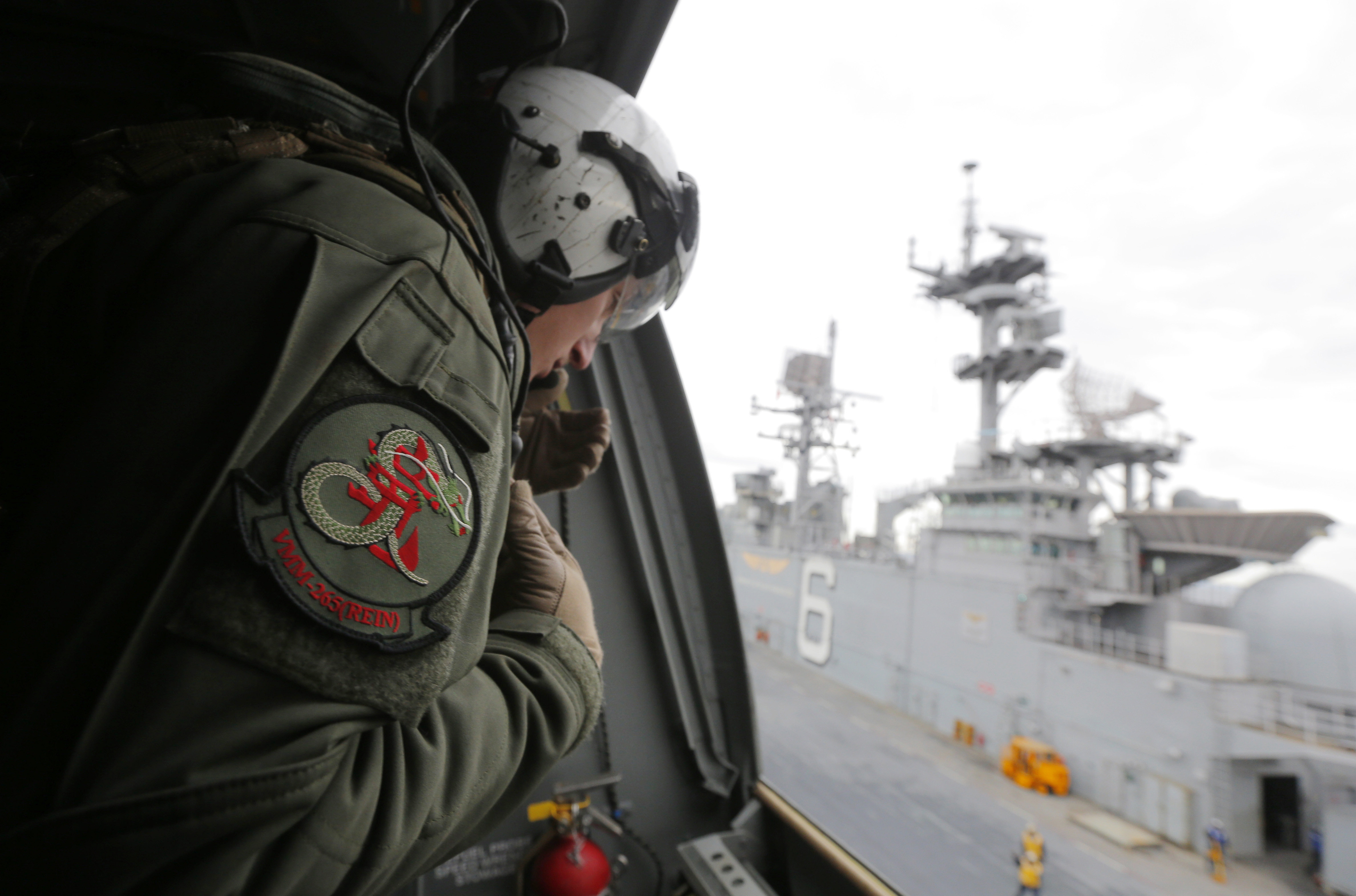 A crewman aboard a U.S. Marine MV-22B Osprey aircraft looks out as it lifts off the deck of the USS Bonhomme Richard amphibious assault ship off the coast of Sydney, Australia, Thursday, June 29, 2017 after a ceremony on board the ship marking the start of Talisman Saber 2017, a biennial joint military exercise between the United States and Australia