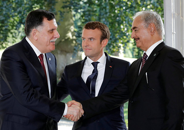 French President Emmanuel Macron stands between Libyan Prime Minister Fayez al-Sarraj (L), and General Khalifa Haftar (R), commander in the Libyan National Army (LNA), who shake hands after talks over a political deal to help end Libya's crisis in La Celle-Saint-Cloud near Paris, France, July 25, 2017