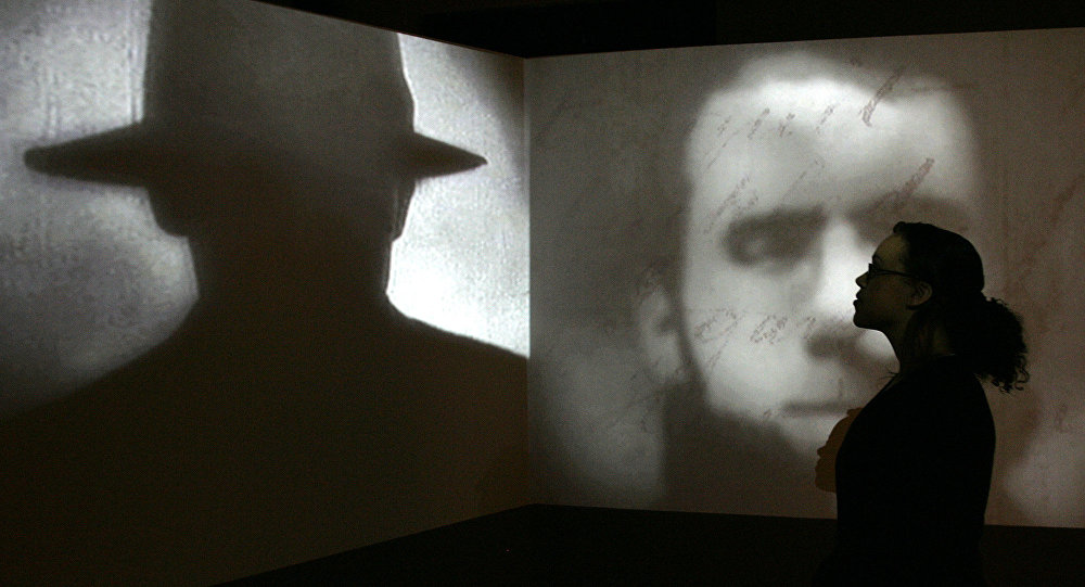 A member of staff poses stands in front of a screen showing a short movie about Jack the Ripper during a press preview for the exhibition Jack the Ripper and the East End at the Museum in Docklands, London, Wednesday, May 14, 2008.