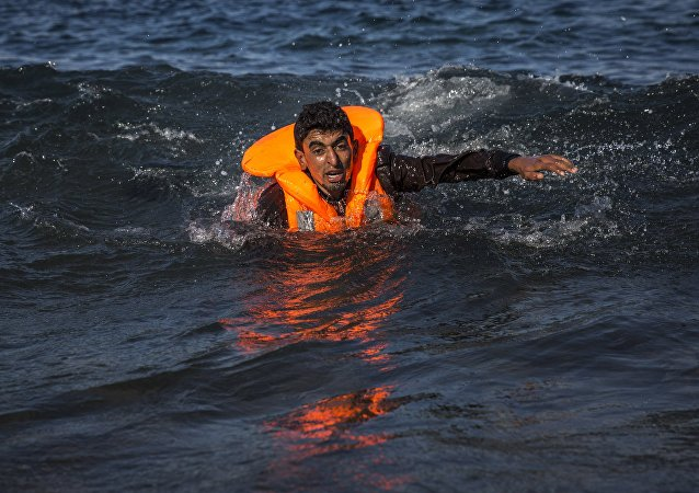 A migrant swims as he arrives on the island of Lesbos after crossing the Aegean sea from Turkey to Greece on an overcrowded inflatable boat , Tuesday, Oct. 27, 2015