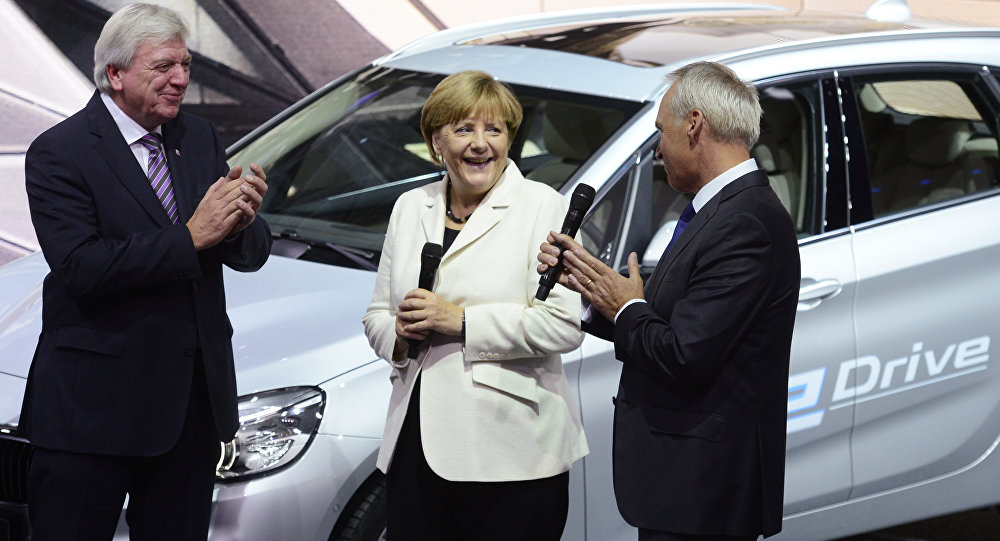 German Chancellor Angela Merkel talks to BMW CFO Friedrich Eichiner, right, as Hesse state governor Volker Bouffier, left, applauds on the first day of the Frankfurt Auto Show IAA in Frankfurt, Germany, Thursday, September 17, 2015.