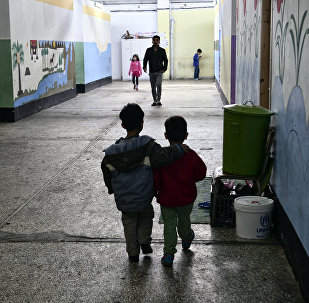 Children walk through a former industrial warehouse at the Oinofyta refugee camp, some 60 km north of Athens, on 13 March 2017 in Oinofyta