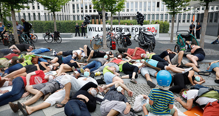 Environmental activists wearing respiratory masks against air pollution perform in front of the Interior Ministry, venue of a so-called diesel summit on August 2, 2017 in Berlin