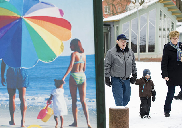 People walk along a snow covered street past an advertisement featuring a pictures of a beach scene in Mariehamn. (File)