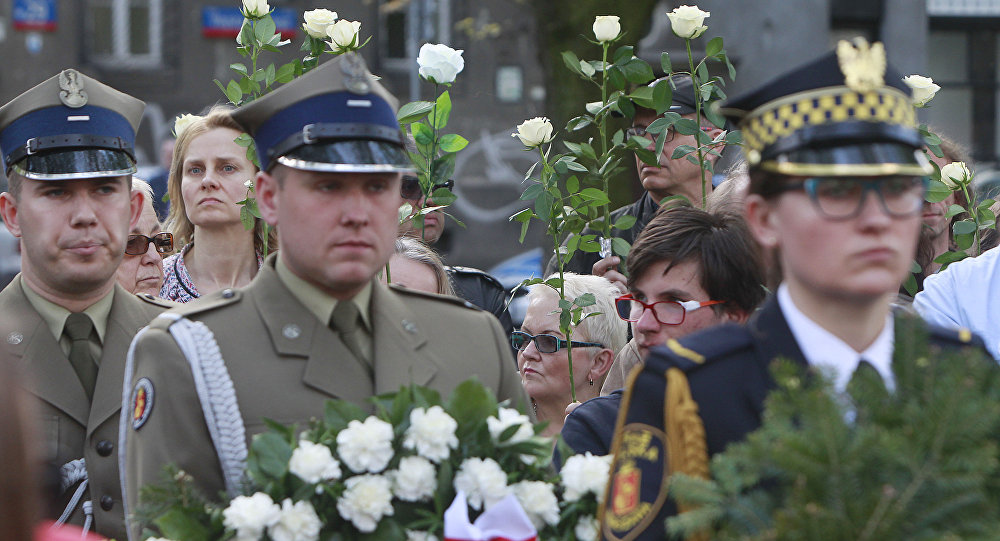 A Polish Army junior officers and Warsaw residents hold flowers during a ceremony to unveil a monument for for World War II hero, Capt. Witold Pilecki, who volunteered to go to Auschwitz and report on the atrocities there, and was later killed by Poland's communist regime,, in Warsaw, Poland, Saturday, May 13, 2017.