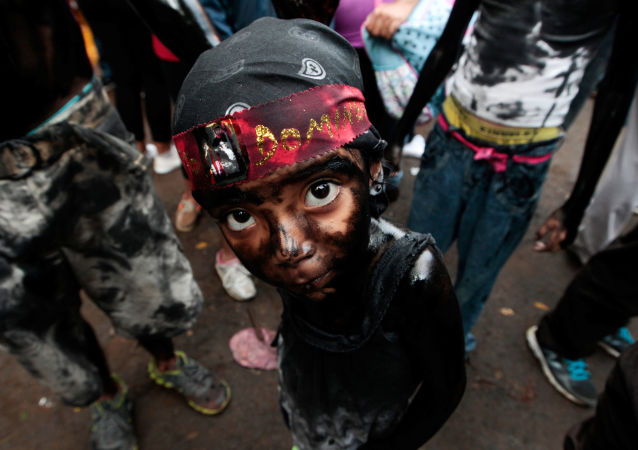 A girl covered in motor oil takes part in the festivities honouring the capital's patron saint Santo Domingo de Guzman in Managua, Nicaragua