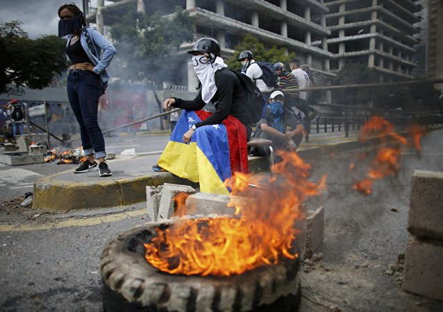 Masked anti-government demonstrators stend to a burning barricade during a protest against the installation of a constitutional assembly in Caracas, Venezuela, Friday, Aug. 4, 2017