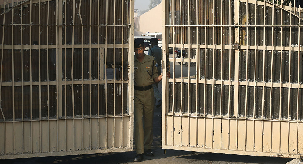 An Indian police officer prepares to close one of the gates at Tihar Jail, the largest complex of prisons in South Asia, in New Delhi, India, Monday, March 11, 2013