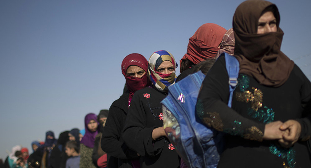 Displaced women queue to receive food after arriving in the Hassan Sham camp, east of Mosul, Iraq, Friday, Nov. 4, 2016