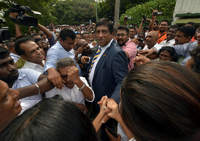 Sri Lanka's foreign minister Ravi Karunanayake reacts as he is surrounded by his supporters after he resigned on Thursday over corruption charges, in Colombo, Sri Lanka August 10, 2017