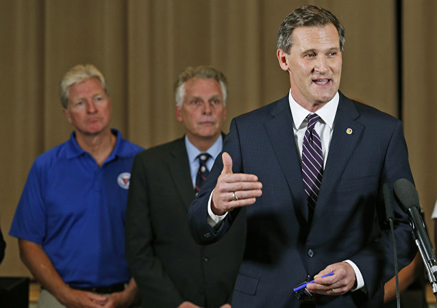Charlottesville Mayor Mike Signer, right, gestures during a news conference concerning the white nationalist rally and violence as Virginia Gov. Terry McAuliffe, center, and Virginia Secretary of Public safety Brian Moran, left, listen in Charlottesville, Va
