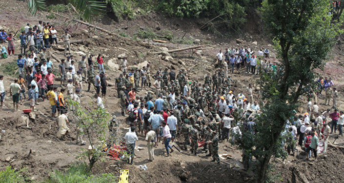 People watch army soldiers and rescue workers recover bodies of landslide victims even as they try to pull out two buses that were covered in mud after a landslide triggered by heavy monsoon rain in Urla village, Himachal Pradesh state, India